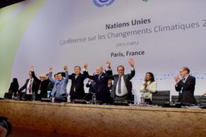 Several world leaders meet at the UN in Paris. Some have their hands linked and raised above their heads. Two others are clapping.