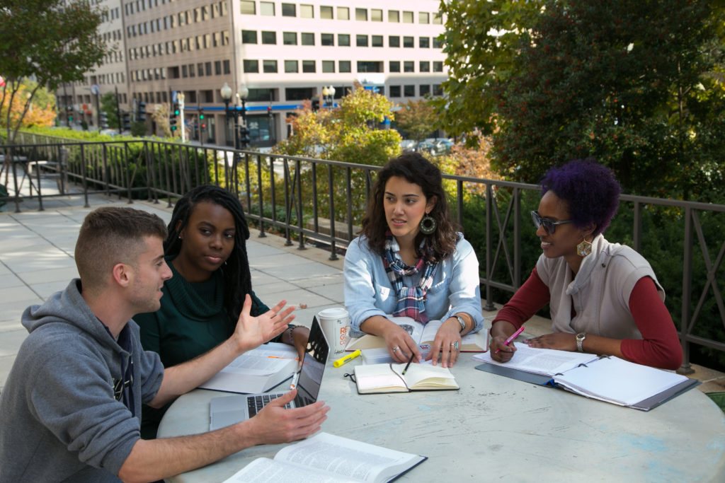 four students studying together outside