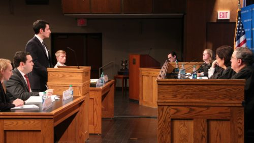 Side view of a student speaks at a podium in front of a panel of judges, co-counsel, and opposing counsel.