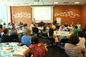 Juvenile Justice Initiative participants sit at tables during a brainstorming session
