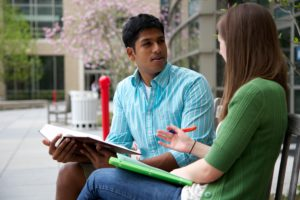 Two students talking on a bench outside Sports and Fitness Center