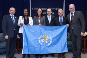 Professor Lawrence O. Gostin, center right, displays the World Health Organization flag with guests at the tenth anniversary celebration of the O'Neill Institute for National and Global Health Law at Georgetown Law.