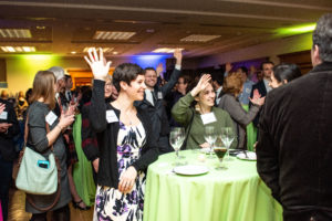 Current and former staff of the Georgetown Climate Center raise their hands.