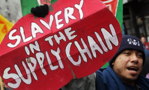 """Farm worker holding a sign that says, """"Slavery in the Supply Chain"""""""