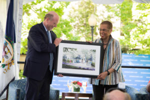 Dean William M. Treanor presents Congresswoman Eleanor Holmes Norton (H'18) with an artist's depiction of a planned bench and memorial to honor Norton, a professor at Georgetown Law for 36 years. (Rendering by Jeff Stikeman for Robert A.M. Stern Architects.)