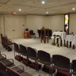 Chairs, altar, and podium arranged for a service in the St. Thomas More Chapel