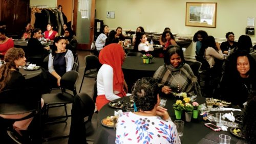 Staff, Faculty, and Students seated around small lunch tables and listening to a speaker
