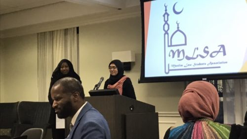 Two students stand at a podium to address students, faculty, and staff at the 2019 Muslim Law Students Association end of year banquet