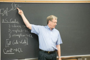 Professor Charles Abernathy teaches in front of a blackboard.