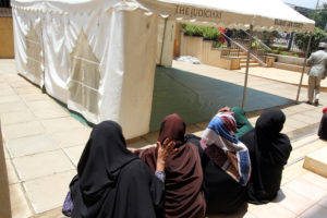 Stock photo of Muslim women next to a tent outside a Nairobi court. In the spring of 2019, the High Court of Kenya ruled that many of the nation's laws violate the constitutional rights of children of unmarried parents. Alumni of Georgetown Law's International Women's Human Rights Clinic filed the complaint in the case back in 2013.