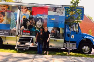 "Rachel North (L'20) and her client, Ella Barnes-Williams (left), in front of the MedStar Georgetown Community Pediatrics' Kids Mobile Medical Van earlier this year. Barnes-Williams's family saw a Georgetown pediatrician and received a ""legal check-up,"" resulting in a referral to the Health Justice Alliance Law Clinic. In Spring 2019, North helped to secure needed educational evaluations and services for Barnes-Williams's grandson."