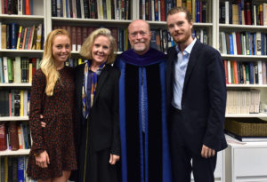 Katherine Treanor, Allison Treanor, Dean William M. Treanor and Liam Treanor in front of a bookcase in the dean's office.