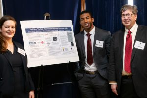 "Rachel Wehr (L'20), Tech Law Scholar Kendall Spencer (L'20) and Professor Matt Blaze with the poster entitled: ""Holding Vendor Machine Voters Accountable: How State Attorneys General Can Help Secure America's Elections."""