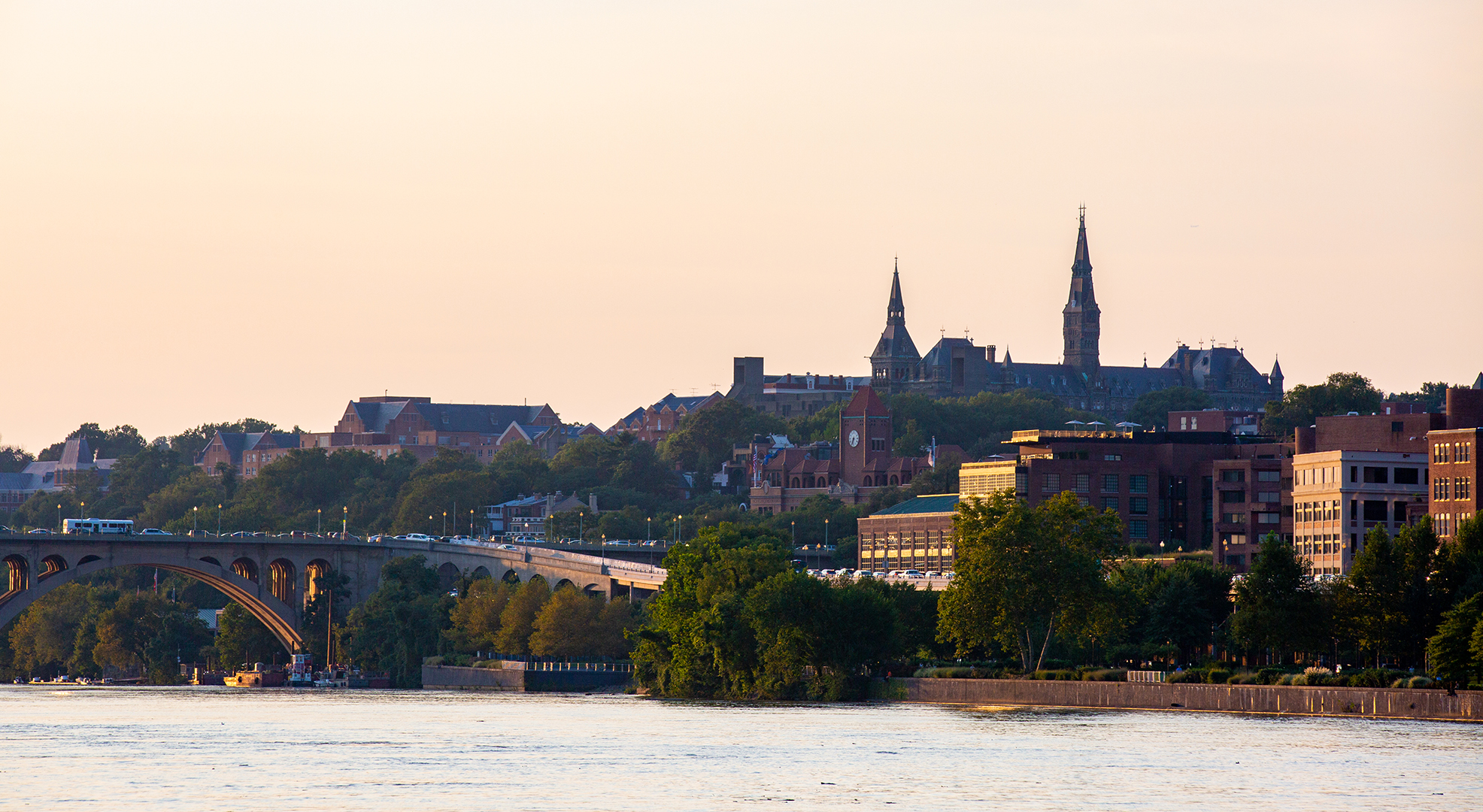 Photo of Georgetown University campus overlooking the river at sunset.