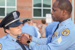 A New Orleans police officer affixes a pin to an officer's uniform after completing peer intervention training.
