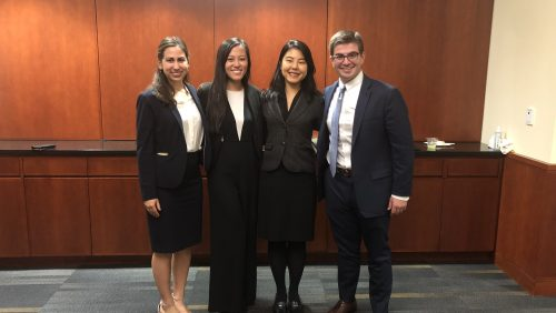 Four students standing together, smiling, in suits