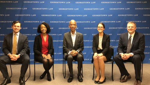 Five people seated in front of blue background with the words GEORGETOWN LAW on it.