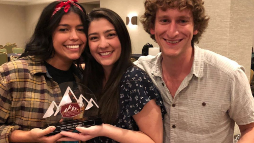 Three students, casually dressed, smiling holding awards. The awards are shaped like mountains and are clear.