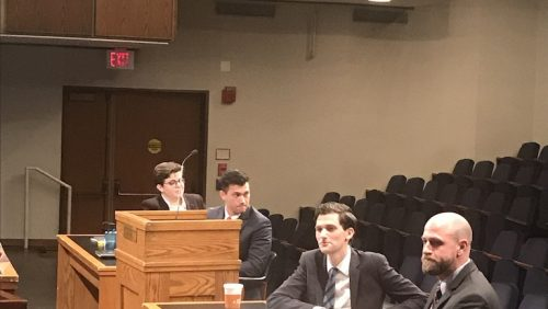 In Hart Auditorium, Courtroom set up, two people per table. The two individuals in the foreground are looking straight ahead while the two in the background are turned around and looking behind them
