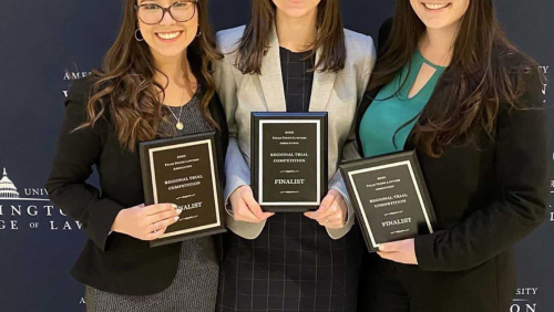 Three students, all wearing glasses, holding three plaques that read the word finalist on it. They are standing in front of a blue background with the words American University Washington College of Law