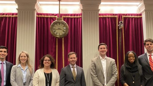Seven people in suits smiling in front of columns and under a clock