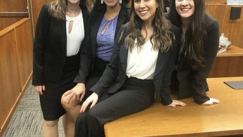 Four women in suits sitting on a table smiling