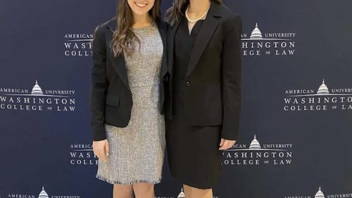 Two women smiling in front of American University Washington College of Law Banner