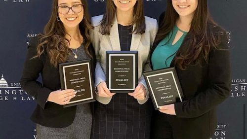 Three women smiling with plaques in front of American University Washington College of Law Banner
