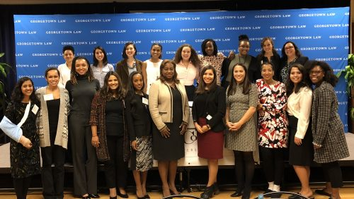 Students, faculty, and staff stand before a Georgetown Law banner and face the camera at the 2018 Women of Color Collective Dinner