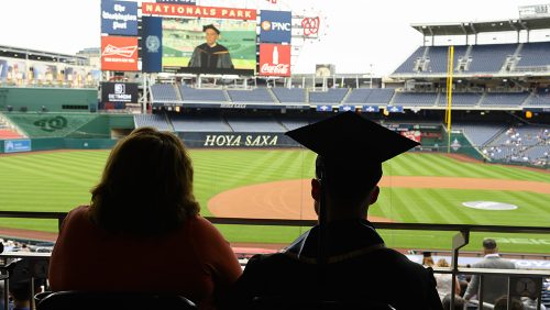 Students watch commencement on the jumbotron at Nationals stadium.