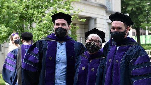 Three graduates wearing masks posing on the Tower green.