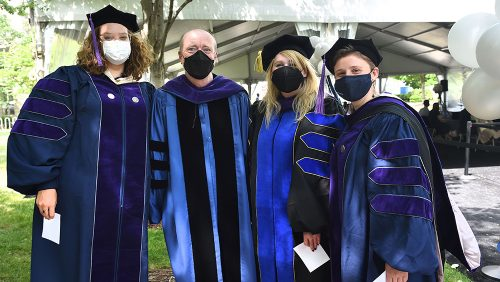 Dean Treanor poses with family members outside of Hart during commencement celebrations.