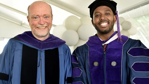 Dean Treanor posing with student for a photo at BLSA graduation ceremony.