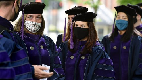 Students wear masks as they line up before walking on the stage for commencement proceedings.