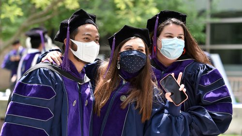 Graduates pose for photo with masks.
