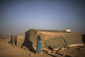 A Syrian refugee mother holds her daughter while standing outside her tent in a tented settlement in Jordan (photo by Muhammed Muheisen).