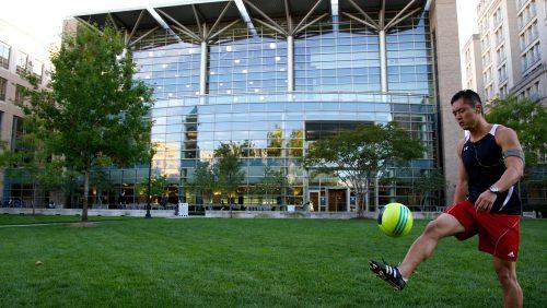 student kicking soccer ball in front of the Scott K. Ginsburg Sport & Fitness Center