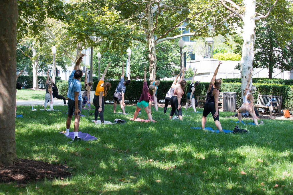 Students gather outside for outdoor yoga.