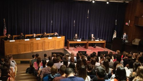 """Faculty presented a moot court preview of an upcoming Supreme Court case. Left to right: """"Justices"""" Professors Paul Smith, Paul Butler, Michael Seidman, Christy Lopez and Irving Gornstein, """"Advocates"""" Dean Erica Hashimoto and Professor Michael Gottesman and master of ceremonies Dean Mitch Bailin."""
